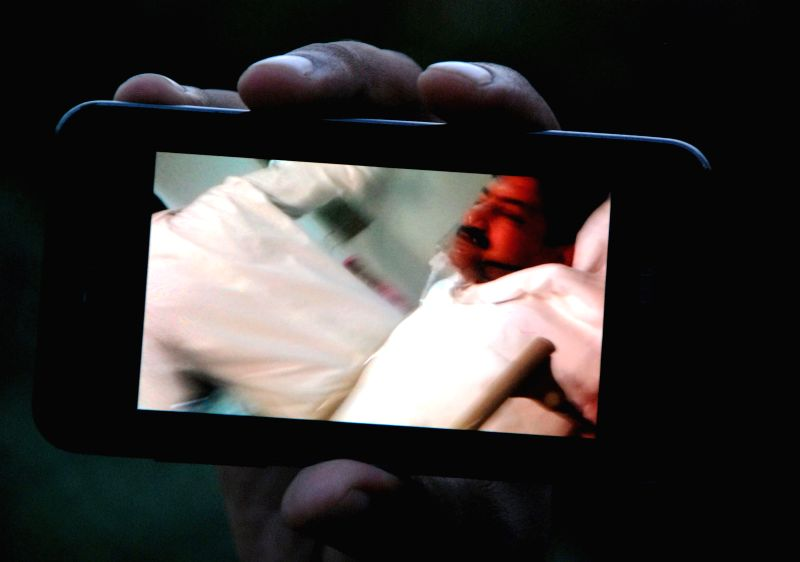 A man shows the image of injured journalist Hamid Mir on his mobile phone at a hospital in southern Pakistani port city of Karachi on April 19, 2014. Prominent ...