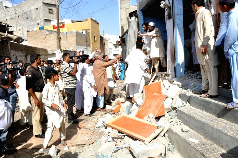 People inspect the blast site in southern Pakistani port city of Karachi on April 24, 2014. At least four people were killed and 15 others injured when a bomb ...
