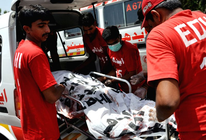 Rescuers transfer a body of a policeman to a hospital in southern Pakistani port city of Karachi, April 24, 2014. At least four people were killed and 15 others ...