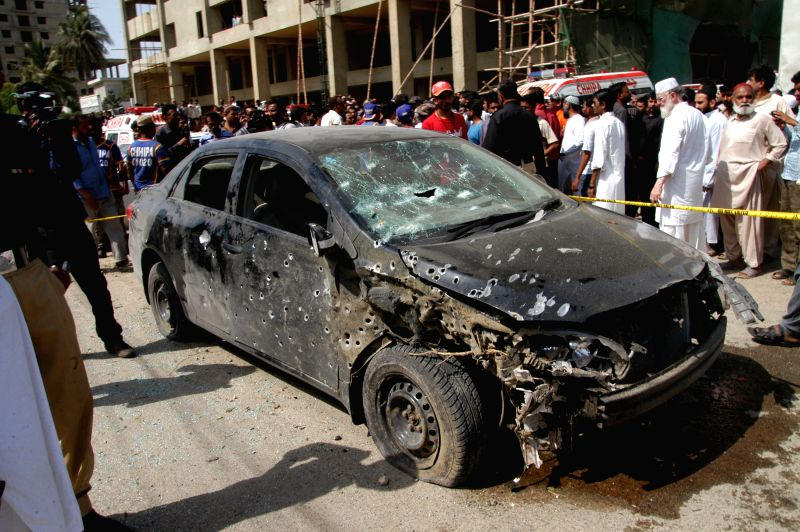 People gather around a destroyed vehicle at the blast site in southern Pakistani port city of Karachi on April 25, 2014. At least four people were killed and over .