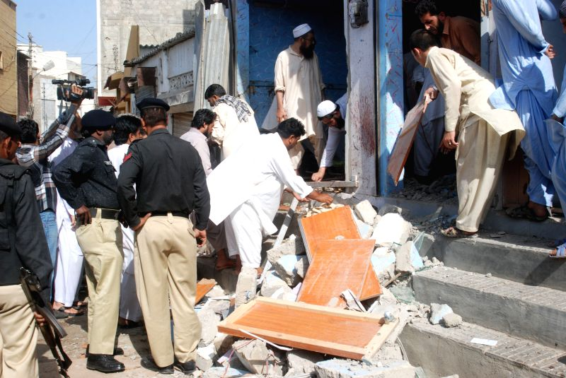 Policemen inspect the blast site in southern Pakistani port city of Karachi on April 24, 2014. At least four people were killed and 15 others injured when a bomb ..