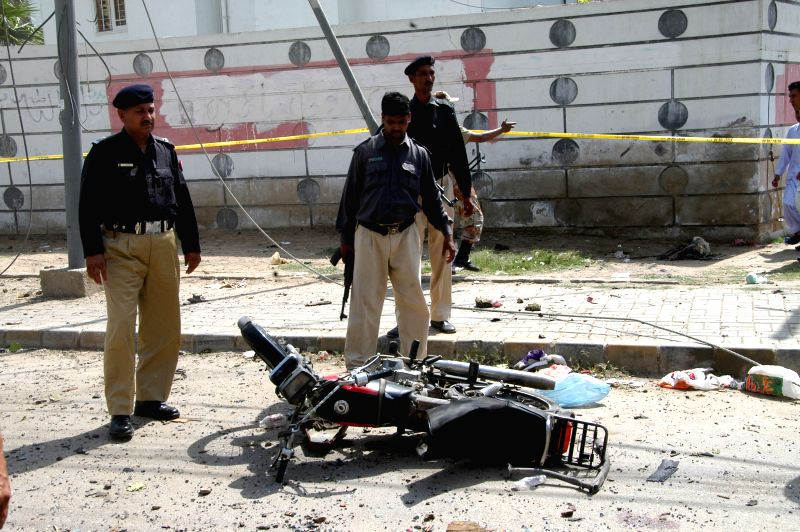 Policemen inspect a destroyed motorbike at the blast site in southern Pakistani port city of Karachi on April 25, 2014. At least four people were killed and over ..