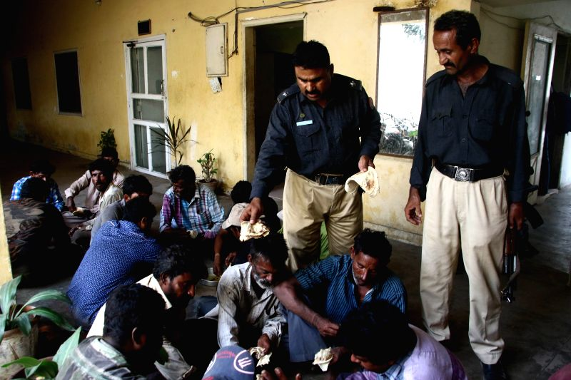 KARACHI, April 27, 2017 - A policeman distributes food to arrested Indian fishermen at a police station in southern Pakistani port city of Karachi, on April 27, 2017. Pakistan's Maritime Security ...