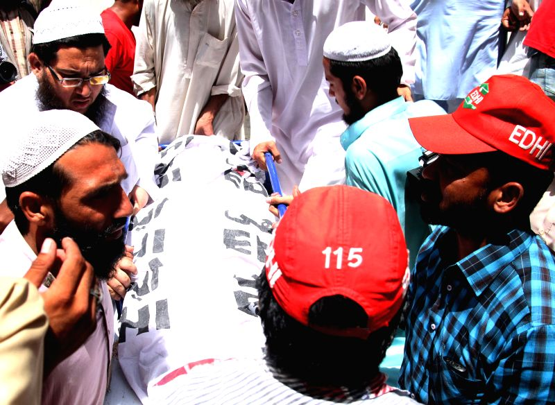 People transfer a body of a seminary kid to a hospital in southern Pakistani port city of Karachi on April 28, 2014. At least four seminary children were killed ...