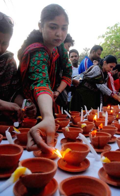 Pakistani people light oil lamps to pay tribute to Pakistani paramilitary soldiers who were killed in their duties on the Martyrs Day in southern Pakistani port ...