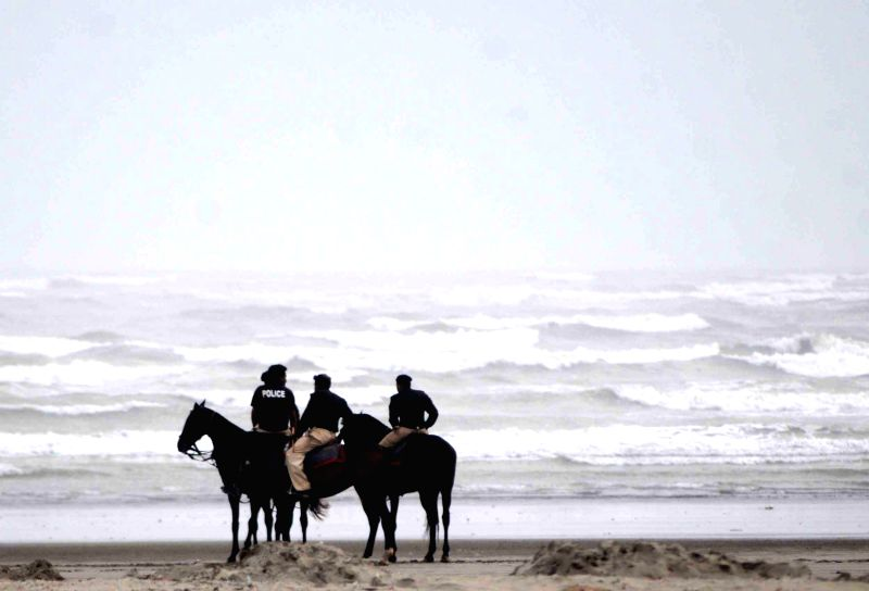 Pakistani policemen take part in a search operation for drowning victims over Clifton beach in southern Pakistani port city of Karachi on July 31, 2014. The bodies ..