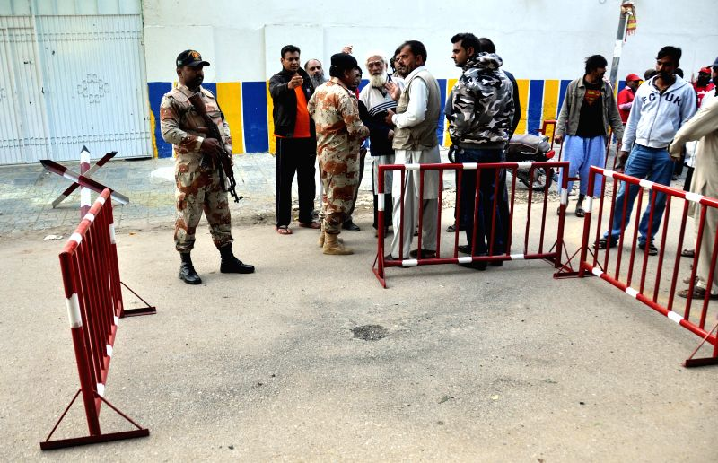 Security officers stand guard outside a private school in southern Pakistani port city of Karachi, Feb. 3, 2015. Unknown militants threw a hand grenade at a school ..