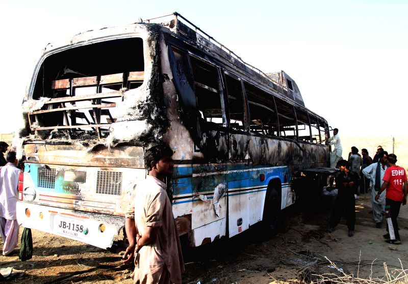 Pakistani people examine a burnt out passenger bus after it collided with an oil tanker along the Super Highway near southern Pakistani port city of Karachi, Jan. ..