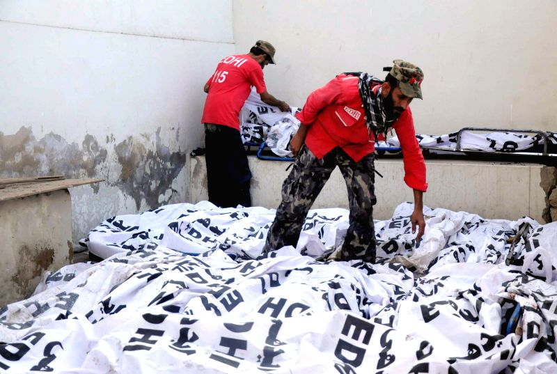 Pakistani volunteers gather beside the bodies of victims at a hospital in southern Pakistani port city of Karachi, Jan. 11, 2015. At least 59 people were killed and