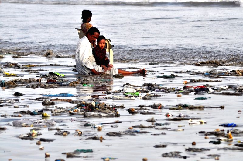 KARACHI, June 5, 2017 - A man with his children sits at a beach littered with wastes in southern Pakistani port city of Karachi, on June 5, 2017.