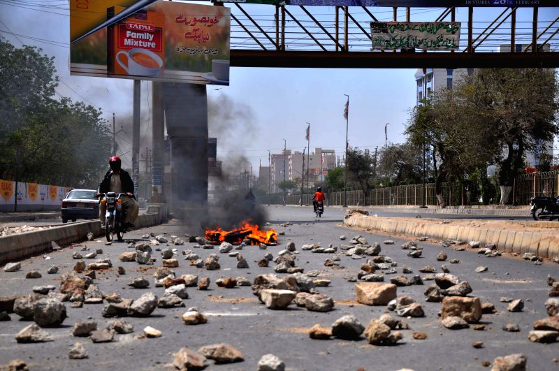 People ride past burning tires and stones on road during a strike called by Muttahida Qaumi Movement (MQM) leaders after a raid on MQM headquarters in southern ...