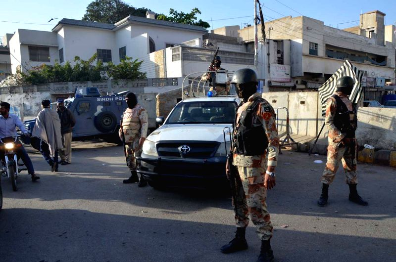 Pakistani paramilitary soldiers cordon off a street during a raid on the offices of the Muttahida Qaumi Movement (MQM) political party in southern Pakistani port ...