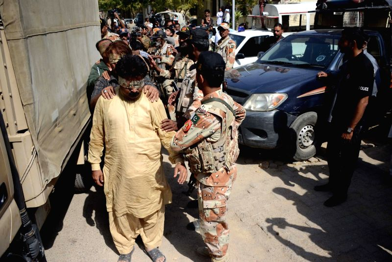 Pakistani paramilitary officials escort blindfolded activists of Muttahida Qaumi Movement (MQM) political party to a court in southern Pakistani port city of ...