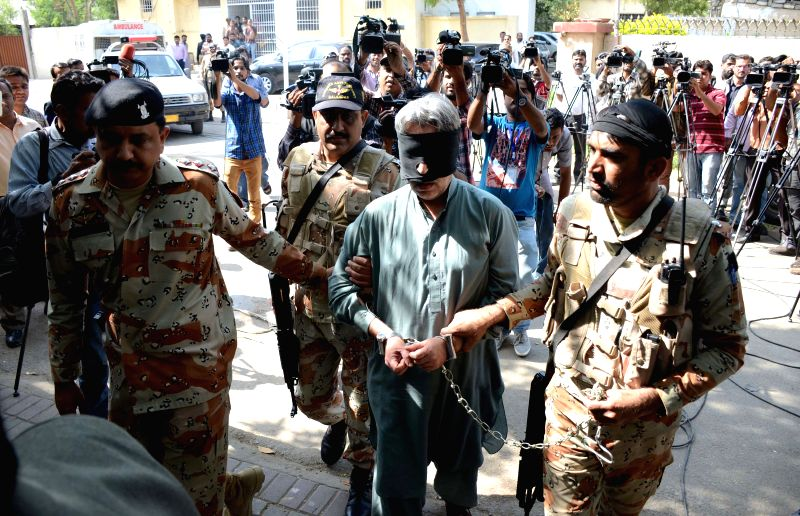 Pakistani paramilitary officials escort blindfolded Aamir Khan (C), leader of Muttahida Qaumi Movement (MQM) political party, to a court in southern Pakistani port ... - Aamir Khan