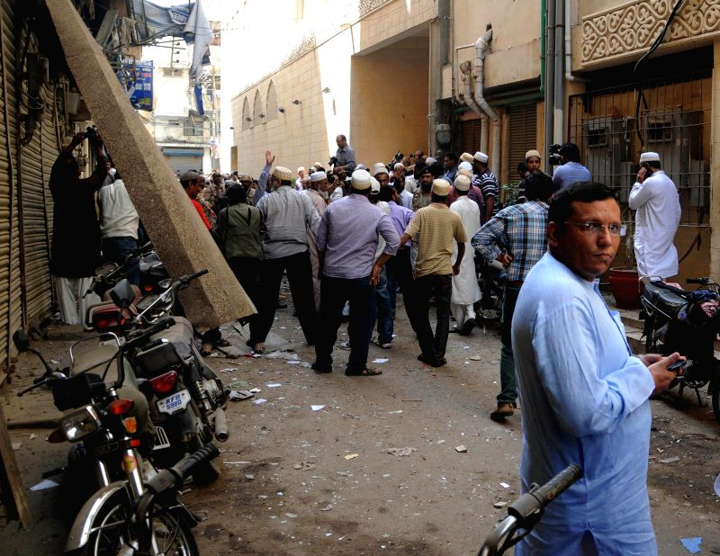People gather at the bomb blast site in southern Pakistani port city of Karachi, March 20, 2015. At least two people were killed and seven others injured when a ...