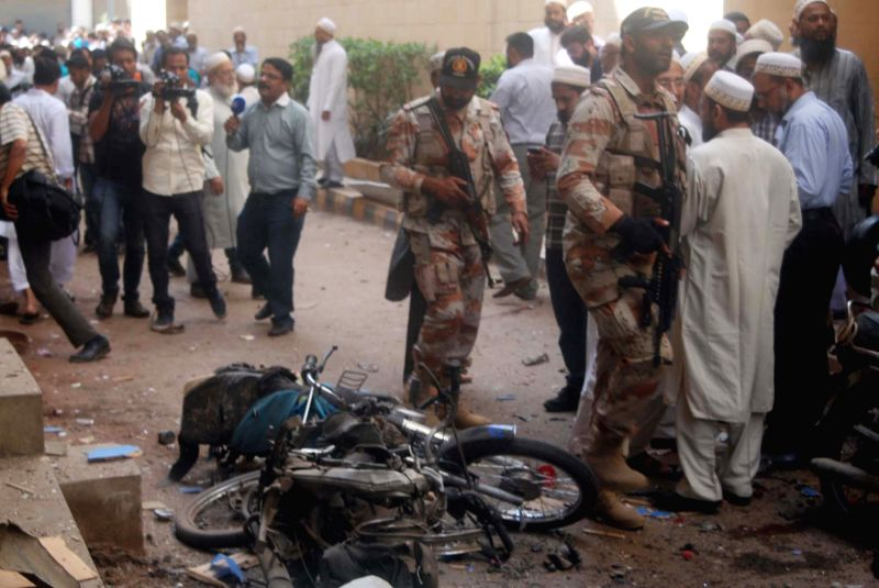 Police rangers inspect the bomb blast site in southern Pakistani port city of Karachi on March 20, 2015. At least two people were killed and seven others injured ...