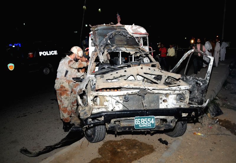 Security officials inspect a damaged vehicle at the blast site in southern Pakistani port city of Karachi on March 20, 2015. At least two Ranger personnels were ...