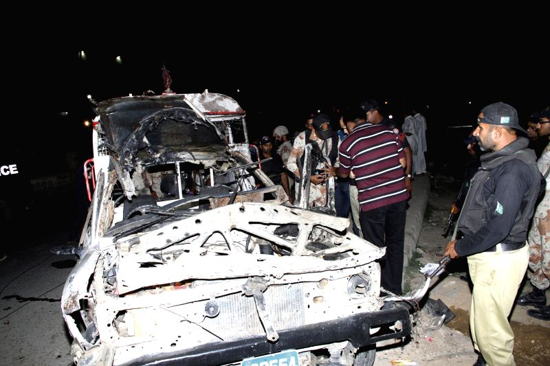 Security officials inspect a damaged paramilitary vehicle at the blast site in southern Pakistani port city of Karachi, March 20, 2015. At least two people were ...