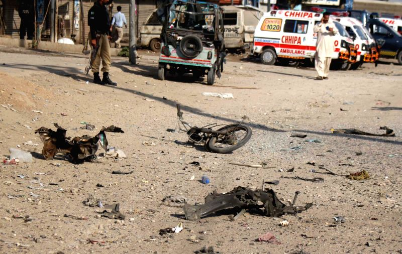 Police officials inspect the blast site in southern Pakistani port city of Karachi, March 27, 2015. At least two policemen were killed and 13 others injured when a ...