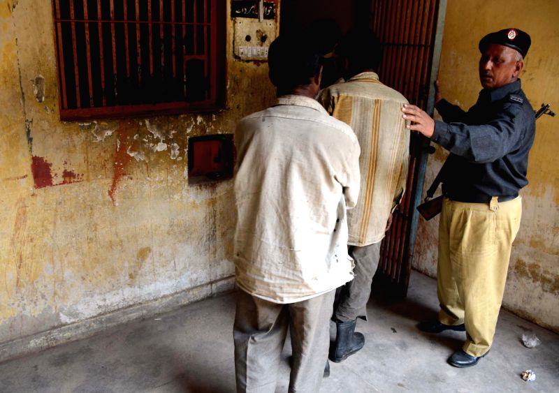 A policeman escorts arrested Indian fishermen to a lockup at a police station in southern Pakistani port city of Karachi, March 6, 2015. Pakistani authorities on ...