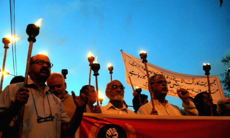 Pakistani laborers take part in a torch rally on the eve of International Labor Day in southern Pakistani port city of Karachi, April 30, 2014.