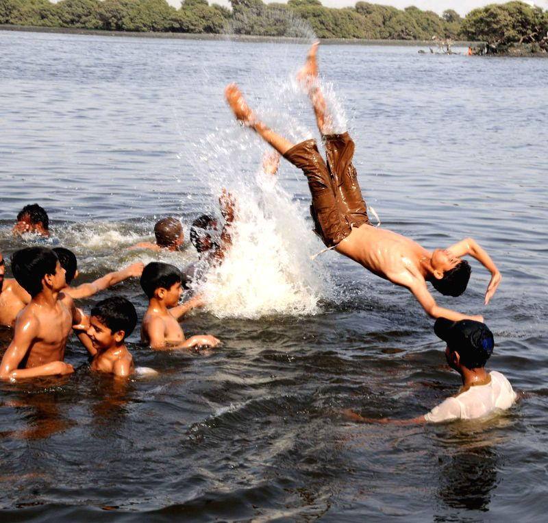 Pakistanis play in a canal during a hot day in southern Pakistani port city of Karachi on May 3, 2015. Temperatures reach over 40 degrees Celsius in many parts of the ...