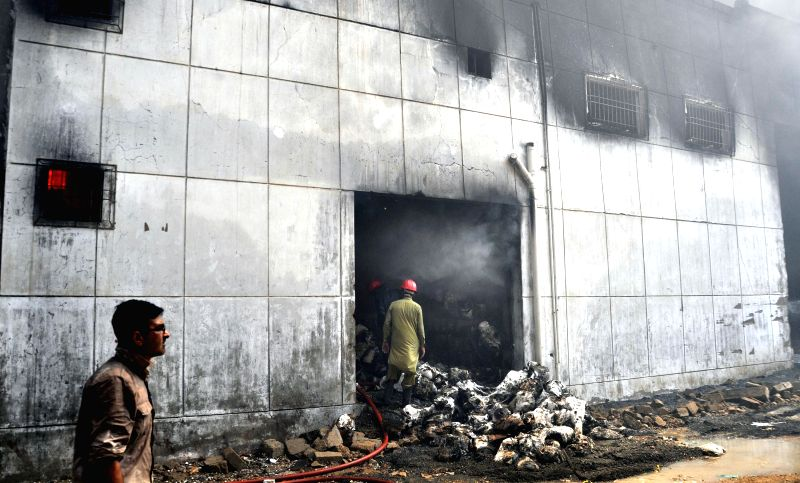 Fire fighters try to extinguish a fire at a garment factory in southern Pakistani port city of Karachi on May 4, 2015. At least 12 workers were injured on Monday as a ...