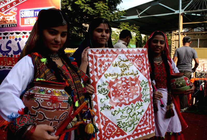 Karachi (Pakistan): Women pose for photos during the Sindh Cultural Day in south Pakistan's Karachi, Dec. 7, 2014. The festival was observed to highlight the culture of Sindh Province, famous for its