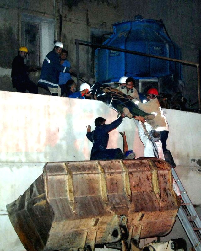 Rescuers carry an injured man at the site of fire accident in southern Pakistani port city of Karachi on Dec. 5, 2014. A textile factory in Karachi caught fire on Friday night. ...