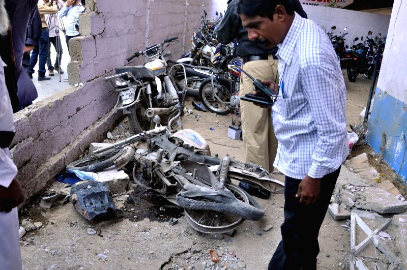 Policemen inspect the blast site in southern Pakistani port city of Karachi, Sept. 3, 2014. At least four policemen were injured when a bomb hit a police check post