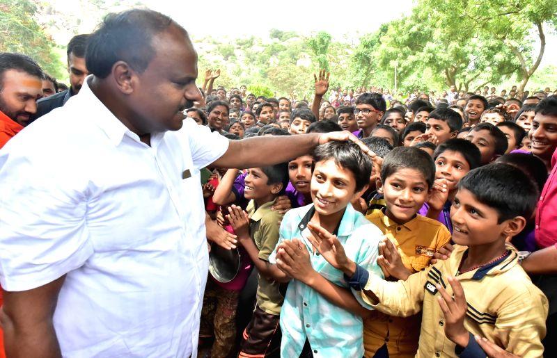 Karnataka Chief Minister H. D. Kumaraswamy interacts with children during his visit to Adichunchanagiri Mutt in Mandya, Karnataka on June 13, 2018. - H. D. Kumaraswamy
