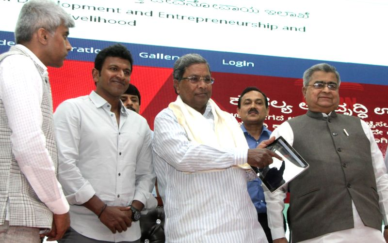 Karnataka Chief Minister Siddaramaiah, actor Puneeth Rajkumar and Karnataka Vocational Training & Skill Development Corportation Ltd KVTSDC Chairman Muralidhar Halappa during the ... - Siddaramaiah