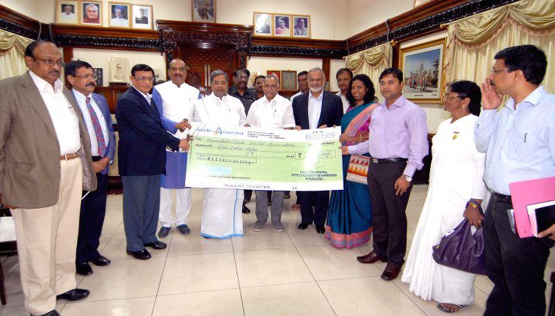 Karnataka Chief Minister Siddaramaiah hands-over a cheque of 1 crore rupees to Karnataka State Cricket Association after Karnataka won Ranaji Trophy in Bangalore on June 27, 2014. - Siddaramaiah