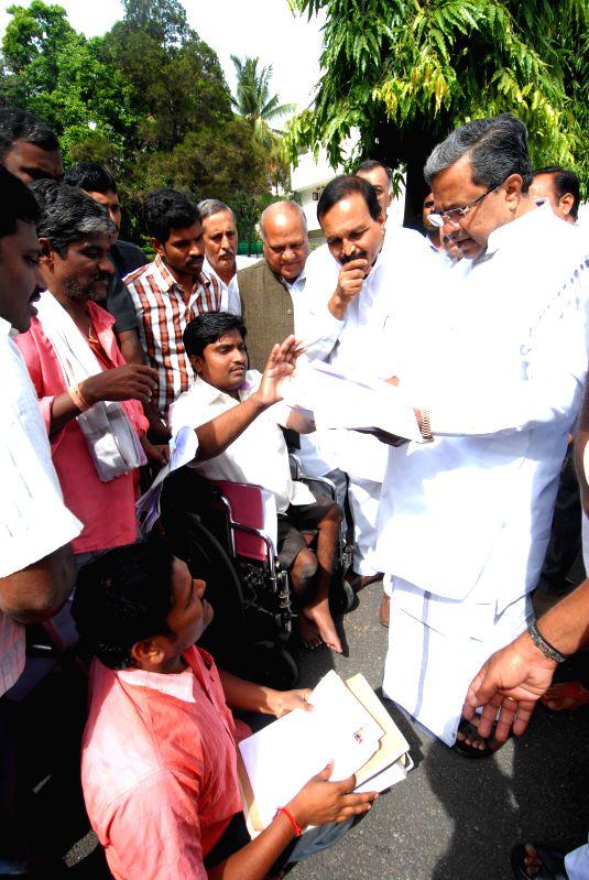 Karnataka Chief Minister Siddaramaiah interacts with public during his `janata darshan` in Bangalore on July 22, 2014. - Siddaramaiah