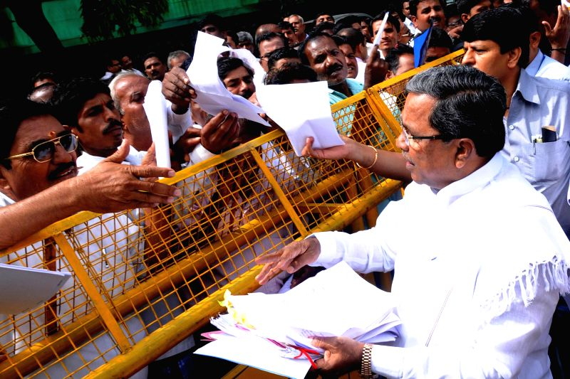 Karnataka Chief Minister Siddaramaiah interacts with public during his `janata darshan` in Bangalore on July 25, 2014. - Siddaramaiah