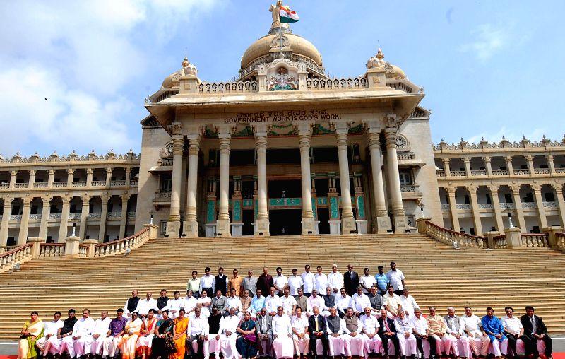 Karnataka Chief Minister Siddaramaiah poses for a photo with Karnataka MLC's in front of Vidhana Soudha in Bangalore on June 30, 2014.