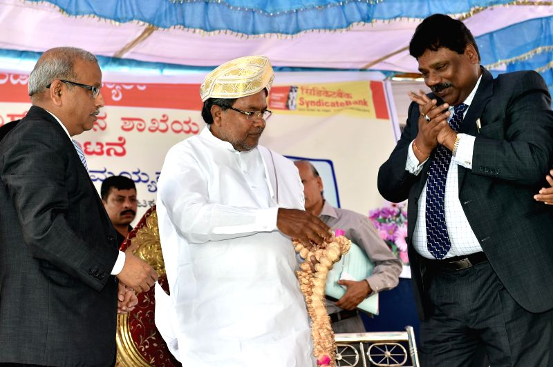 Karnataka Chief Minister Siddaramaiah with Executive Directors of Syndicate Bank M Anjaneya Prasad and TK Srivatsa at the inauguration of a new branch of Syndicate Bank in Bangalore on Aug 26, 2014. - Siddaramaiah