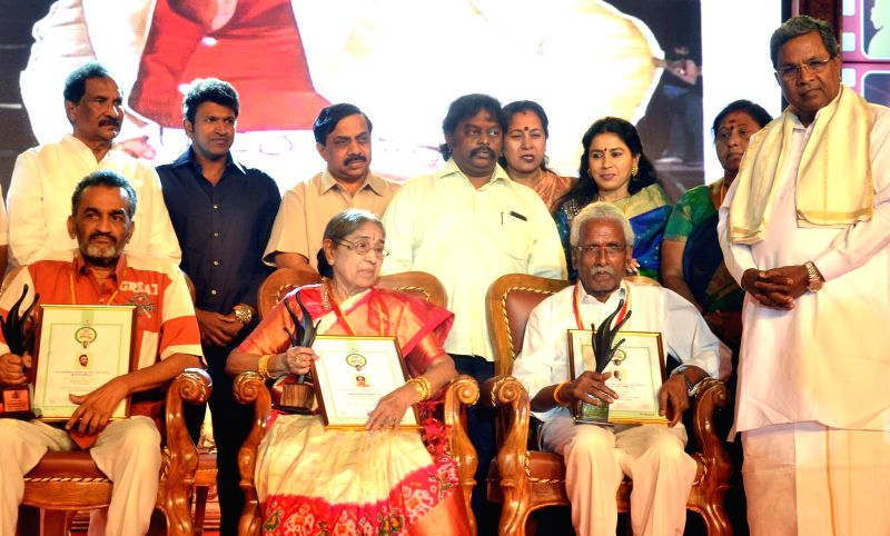 Karnataka Chief Minister Siddaramaiah with filmmaker K.V. Raju, actress Advani Lakshmi Devi and   poster designer K Chinnappa during Karnataka State Film Awards ceremony in Bengaluru, on ... - Siddaramaiah
