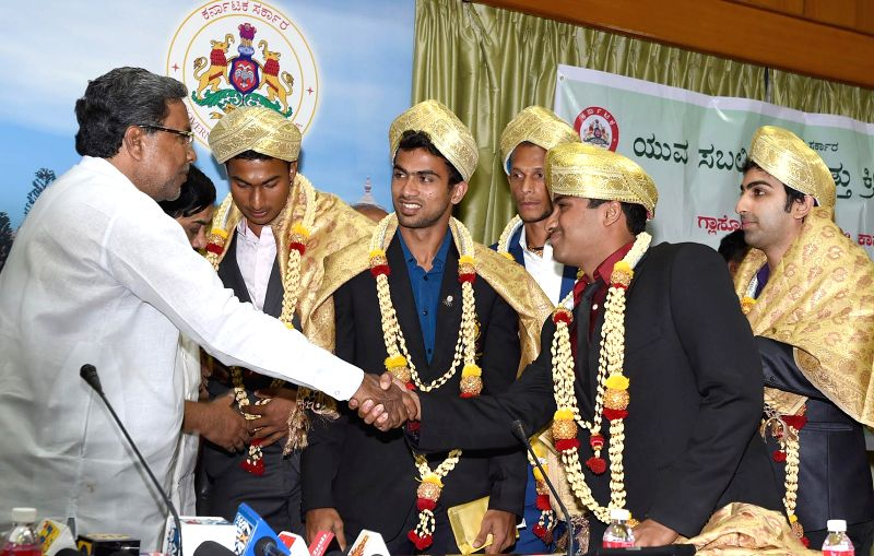 Karnataka Chief Minister Siddaramaiah with medal winners of Glasgow Commonwealth Games during a felicitation programme organised at his office in Bangalore on Aug 25, 2014.