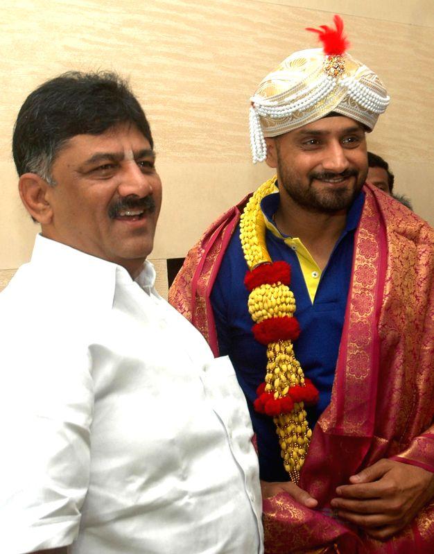 Karnataka Energy Minister, D K Shivakumar greets Indian cricketer Harbhajan Singh in Bangalore on Sept 3, 2014.