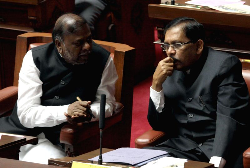 Karnataka Home Minister Dr G Parameshwar interacts with legislature H Anjaneya on the first day of Winter Assembly Session at Vidhan Soudha, in Bengaluru on Nov. 16, 2015.