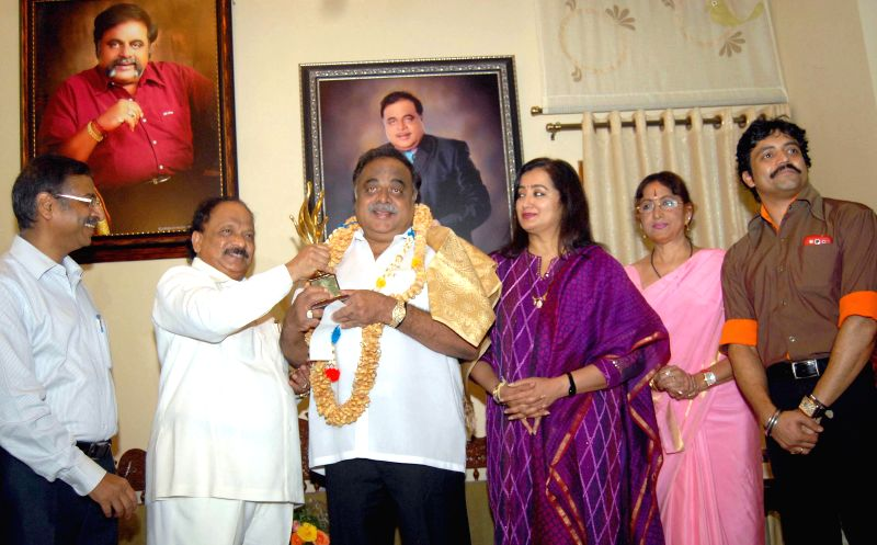 Karnataka Minister for Infrastructure Development and Information R Roshan Baig confers `Dr. Vishnuvardhan` award to Karnataka Housing Minister and actor M.H. Ambareesh and actress Bharathi ... - M. and R Roshan Baig