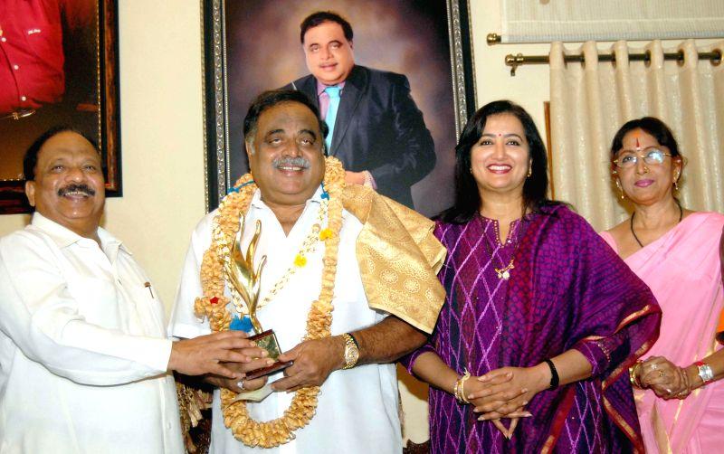Karnataka Minister for Infrastructure Development and Information R Roshan Baig confers `Dr. Vishnuvardhan` award to Karnataka Housing Minister and actor M.H. Ambareesh and actress Bharathi ... - M. and R Roshan Baig