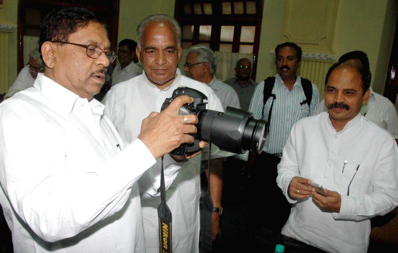 Karnataka Pradesh Congress Committee (KPCC) president Dr. G Parameshwara checks out a camera ahead of a Congress Legislative Party meeting at Vidhana Soudha in Bangalore on June 18, 2014.