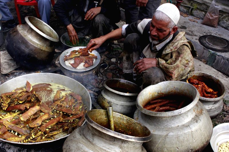 People busy cooking  Wazwan - a Kashmiri cuisine that consists of thirty-six courses in Kashmir valley. The cuisine comprises of Maithi maaz, Rista (meatballs), Lahabi Kabab or Moachi Kabab .