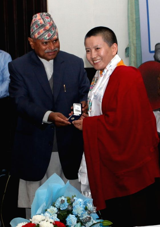 Nepal's President Ram Baran Yadav (L) presents a badge to Nepalese singer Ani Choying Dolma during the appointment of Nepal's United Nation's Children's Fund ...