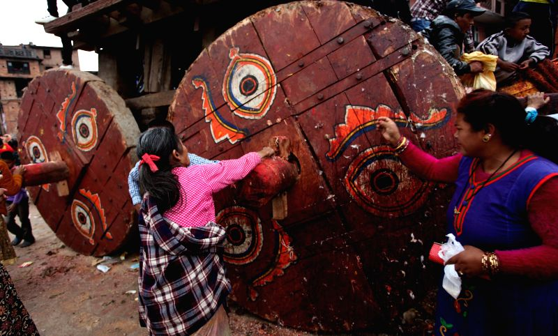 Hindu women offer prayers to chariot of Bhairav near the erected long wooden pole during a celebration of traditional Bisket Jatra Festival in Bhaktapur, Nepal, .