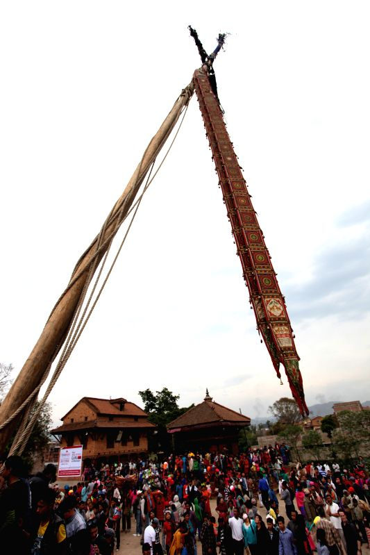 Local children sit on the chariot of Bhairav near the erected long wooden pole during a celebration of traditional Bisket Jatra Festival in Bhaktapur, Nepal, ...