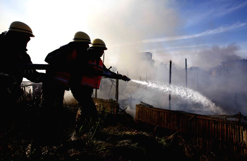 Nepalese army rescue team try to douse a fire at a poultry farm in Bhaktapur, Nepal, April 14, 2015. No casualties were reported and the cause of fire is yet to ...