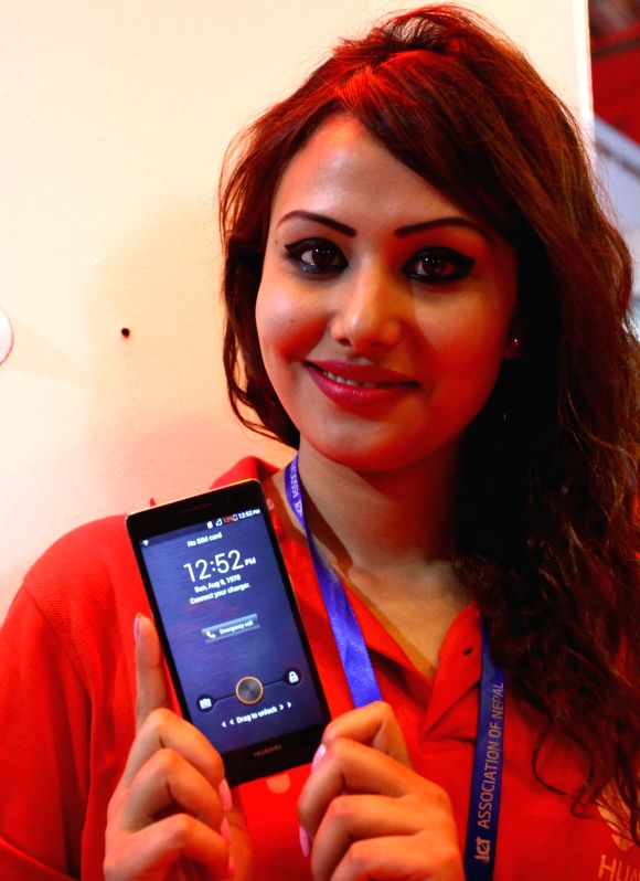 A model shows a new mobile phone at a stall during the 7th ICT Electronics and Branding Expo 2014 at Bhrikutimandap exhibition hall in Kathmandu, Nepal, April ...